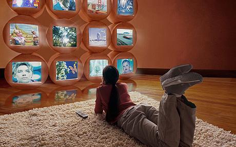 Girl (10-12) lying on floor, watching different TV screens